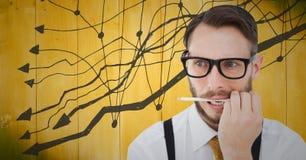 Разочарованный бизнесмен с ручкой в рте против желтых деревянных панели и диаграммы Стоковое Фото