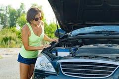 Разочарованный водитель женщины стоит около сломленного автомобиля на проселочной дороге, смотрит проблему, открытый клобук Стоковые Фотографии RF