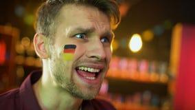 Разочарованный мужской вентилятор с немецким флагом покрашенным на руке щеки развевая, отказе сток-видео