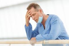 Разочарованный доктор. Подавленный зрелый доктор в голубой равномерной стойке Стоковое Изображение RF