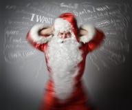 Разочарованный Санта Клаус и много желаний белизна принципиальной схемы изолированная головной болью стоковое изображение