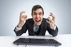 Разочарованный сердитый бизнесмен работает с компьютером в офисе Стоковая Фотография