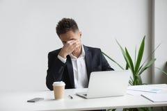 Разочарованный усиленный бизнесмен чувствуя утомлянный компьтер-книжки, глаз fa стоковые фотографии rf