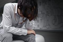 Разочарованный усиленный молодой азиатский бизнесмен при руки покрывая сторону и чувствуя разочарованный или вымотанный с работой Стоковая Фотография RF