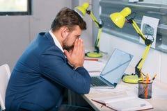 Разочарованный человек сидя на столе в офисе, смотря компьтер-книжку с разочарованным взглядом indoors стоковое фото