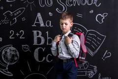 Разочарованный школьник стоя перед доской как предпосылка с рюкзаком на его назад Изображение ландшафта стоковое фото rf