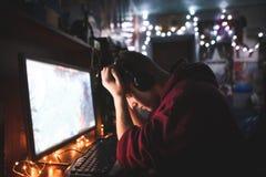 Разочарованный gamer с его опущенными руками теряя в игре Расстроенный подросток сидит на столе компьютера и грустен стоковая фотография