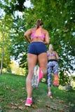 Разработка 2 женщин jogging - фитнес внешний на парке Стоковые Фото