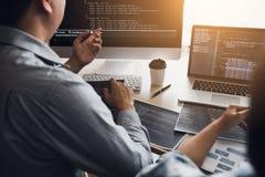 2 разработчика программного обеспечения используют компьютеры для работы вместе с их партнером на столе офиса стоковые фото