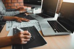 2 разработчика программного обеспечения используют компьютеры для работы вместе с их партнером на столе офиса стоковое изображение