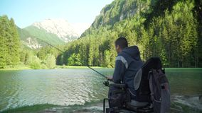 разрешение 4k с ограниченными возможностями рыболова в электрической кресло-коляске удя в красивом озере около леса и горы внутри видеоматериал