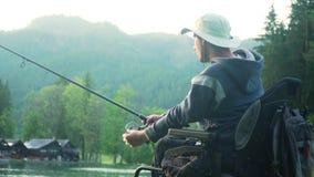 разрешение 4k с ограниченными возможностями рыболова в электрической кресло-коляске удя в красивом озере около леса и горы внутри сток-видео