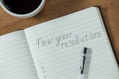 Разрешения Нового Года написанные на дневнике с кружкой кофе Стоковое Изображение RF
