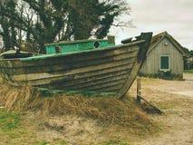 Разрушенная рыбацкая лодка на старой сухой траве Покинутый деревянный корабль с поврежденным двигателем Стоковые Фотографии RF