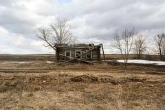 Разрушенный деревянный дом в дезертированной деревне стоковая фотография rf