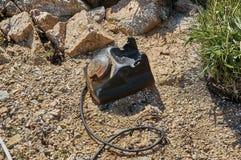 Разрушенный черный телефон на пляже Стоковые Фото