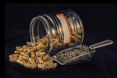 Разрушьте капсулы и высушенную марихуану изолированные над чернотой стоковые фотографии rf