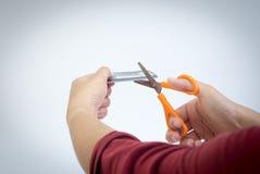 Разрушьте кредитную карточку используя ножницы стоковое фото
