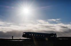 Разрушьте покинутый самолет при путешественник силуэта принимая фото, с ярким солнечным светом с влияниями пирофакела стоковые фото