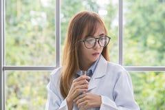Разум духа whit науки голубой Научная синь вещества внутри на ее руке на лаборатории предпосылка Красивые женские доктор или учен стоковые фото