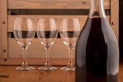 Разлейте по бутылкам и бокал вина на деревянном backgroung Стоковое Изображение