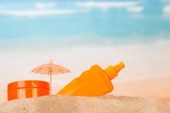 Разлейте солнцезащитный крем по бутылкам, сливк опарника moisturizing, зонтик в песке против моря Стоковое Фото