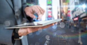 Раздел бизнесмена средний с таблеткой за bokeh против расплывчатой улицы Стоковые Фотографии RF