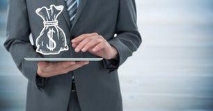 Раздел бизнесмена средний с таблеткой и белые деньги кладут график в мешки против расплывчатой голубой деревянной панели стоковое фото rf