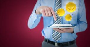 Раздел бизнесмена средний с таблеткой и emojis с пирофакелами против maroon предпосылки Стоковое фото RF
