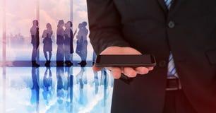 Раздел бизнесмена средний с телефоном против силуэтов и окна Стоковое Изображение RF