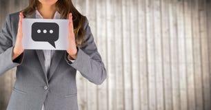 Раздел бизнес-леди средний при карточка показывая график пузыря речи против расплывчатой деревянной панели Стоковые Фотографии RF