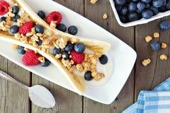 Разделение банана с югуртом, ягодами и granola, выше на древесине Стоковая Фотография