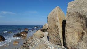 Разделенный утес на человеке пляжа Стоковое Фото