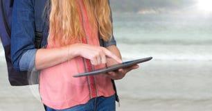 Раздел женщины средний с рюкзаком и таблеткой против расплывчатого пляжа и пирофакела Стоковая Фотография