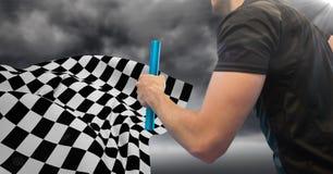 Раздел и пирофакел бегуна реле средний против бурного неба и checkered флага Стоковое Фото