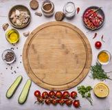 Разделочная доска, вокруг ингридиентов лож для варить вегетарианскую еду, томаты на ветви, специи, огурцы умаслит место для текст Стоковое Изображение RF