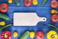 Разделочная доска и свежие овощи на деревянном столе красные и желтые перцы, чили огурца и перцы habanero, томаты стоковая фотография rf