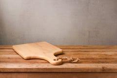 Разделочная доска на деревянной таблице палубы над деревенской предпосылкой стены варить стоковая фотография rf