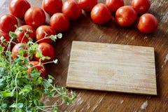 Разделочная доска окруженная томатами Стоковые Изображения