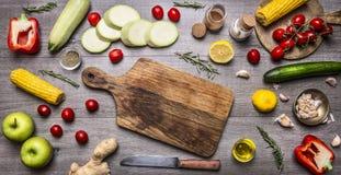 Разделочная доска, положение вокруг огурцов, перцы, томаты на ветви, лимон, мозоль, цукини, яблоки, масло, специи и травы, h Стоковые Изображения RF