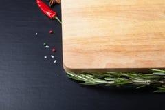 Разделочная доска при покрашенное розмариновое масло, и перец chili, и море s Стоковая Фотография RF