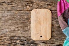 Разделочная доска с салфеткой на деревянной предпосылке Стоковая Фотография