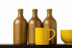 разливает керамические чашки по бутылкам Стоковая Фотография