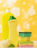 Разливает тензид, губку и яблоко по бутылкам на абстрактной желтой предпосылке Стоковые Изображения RF