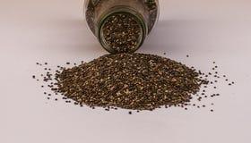 Разливать семян Chia стеклянного опарника на белой предпосылке Стоковые Фотографии RF
