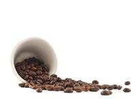 Разлитые кофейные зерна от изолированной чашки Стоковая Фотография