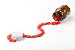 Разлитый от пилюлек стеклянных красного цвета бутылки apothecary Стоковые Изображения
