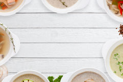 Различная вкусная рамка супов на белом деревянном положении квартиры Стоковое Фото