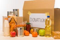 Различная еда с картонной коробкой и пожертвование подписывают на деревянном столе на белизне стоковое изображение rf