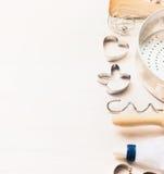 Различная кухня печет утвари с резцом печенья или печенья в форме зайчиков и сердцами на белой деревянной предпосылке Стоковые Изображения RF